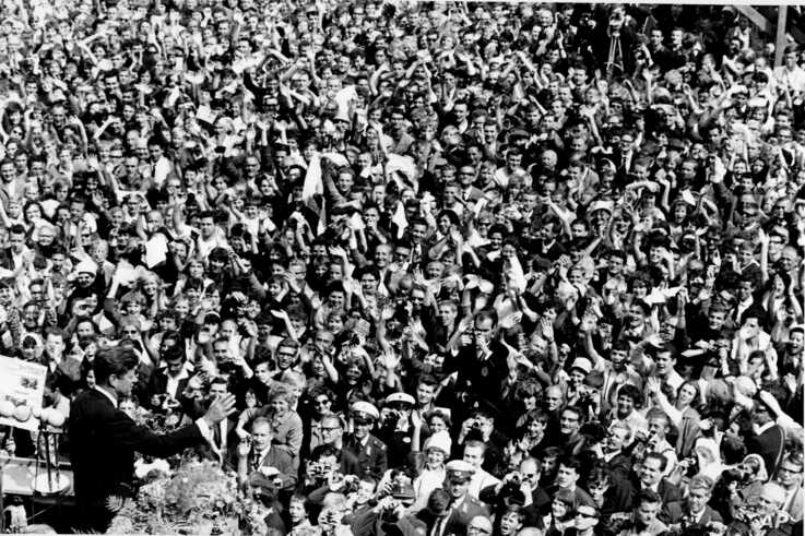 U.S. President John F. Kennedy, left, waves back to a crowd of more than 300,000 persons gathered to hear Kennedy's speech…