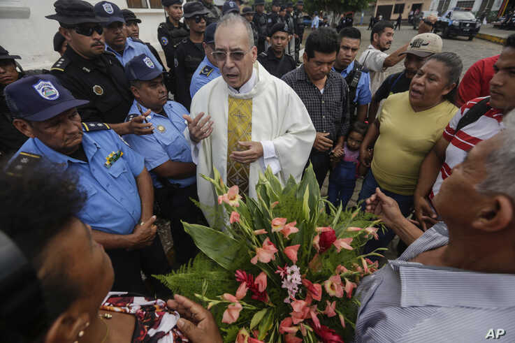 Father Edwin Roman attempts to convince the police to allow relatives of imprisoned and dead anti-government demonstrators to enter the San Miguel Arcangel Church in Masaya, Nicaragua, Nov. 14, 2019.