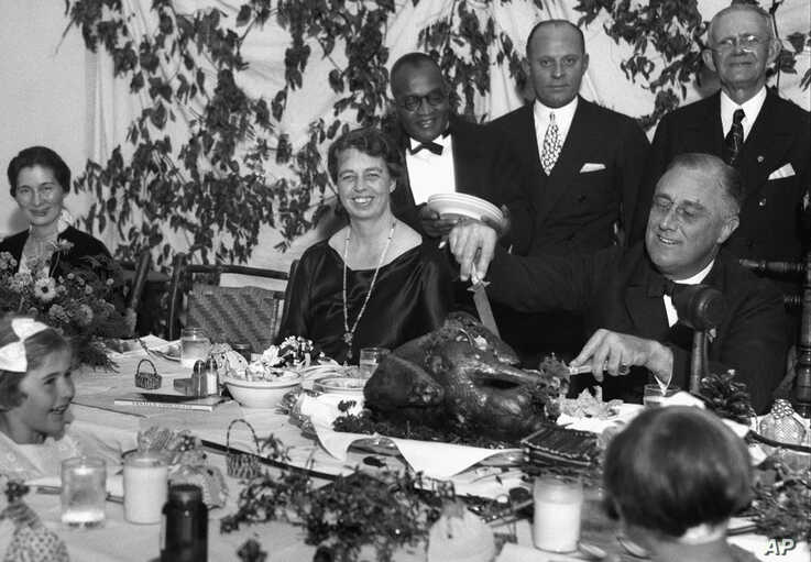 President Franklin D. Roosevelt carves the turkey during Thanksgiving dinner for polio patients at Warm Springs, Ga., with first lady Eleanor Roosevelt beside him, Dec. 1, 1933.