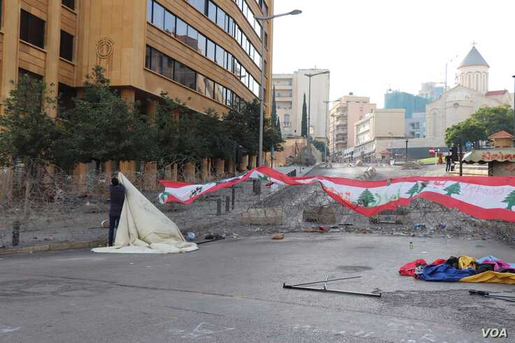 Protesters set up a new tent outside government buildings which are barricaded with barbed wire, in Beirut, Nov. 19, 2019. (Heather Murdock/VOA)