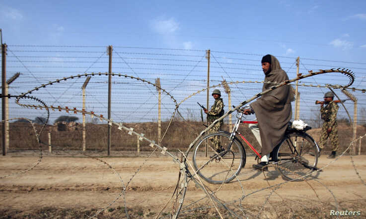 A man rides his bicycle past India's Border Security Force (BSF) soldiers patrolling the fenced border with Pakistan near Jammu…