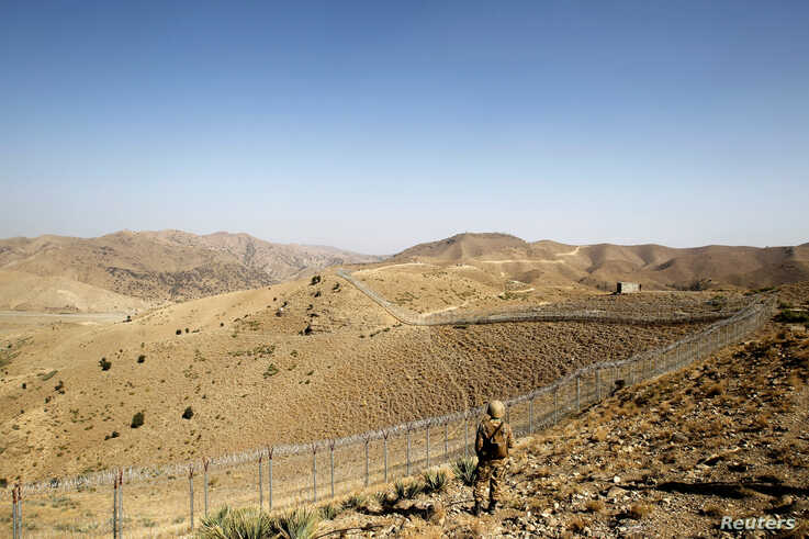 A soldier stands guard along the border fence outside the Kitton outpost on the border with Afghanistan in North Waziristan,…