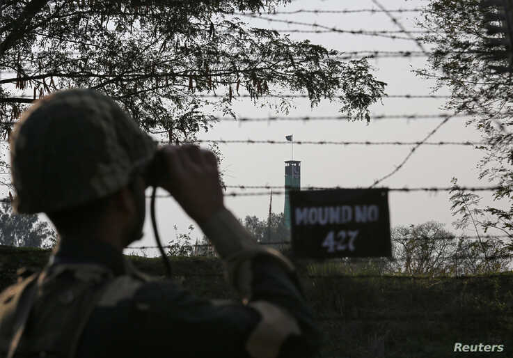 An India's Border Security Force (BSF) soldier keeps vigil during patrol along the fenced border with Pakistan in Ranbir Singh…