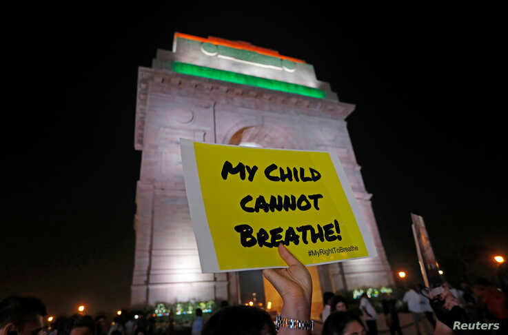 A protestor holds a placard in front of the India Gate during a protest demanding government to take immediate steps to control…