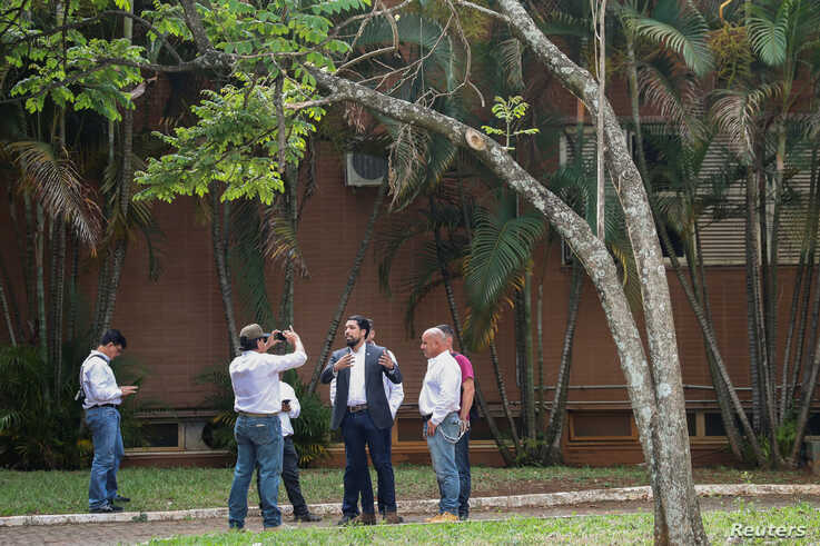Supporters of Venezuela's opposition leader Juan Guaido record a video from the grounds of the Venezuelan embassy in Brasilia,…