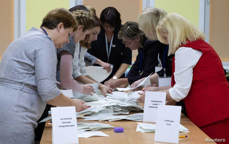 Members of a local election commission sort ballots before starting to count votes after the parliamentary election in Minsk,…