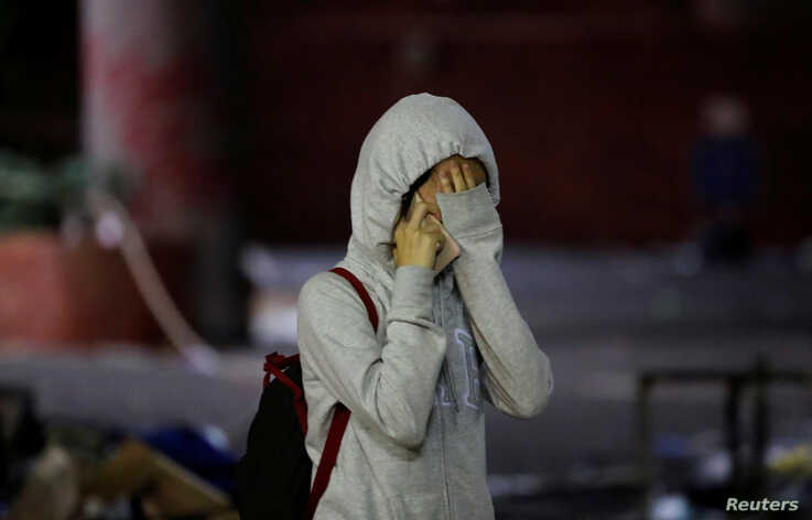 An anti-government demonstrator cries after coming out of the Hong Kong Polytechnic University (PolyU) to surrender, in Hong…