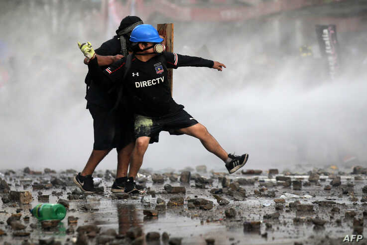 Demonstrators clash with riot police during a protest demanding greater social reform from Chilean President Sebastian Pinera, Nov. 12, 2019.