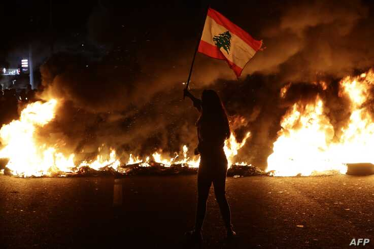 A Lebanese anti-government protester waves a Lebanese flag in front of burning tires that block the main highway linking the city of Tripoli to Beirut at the coastal city of Byblos, north of the capital, Nov. 13, 2019.