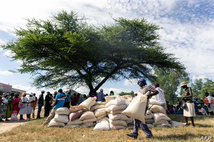 A man carries a full bag of donated maize grain, March 13, 2019, in the Mutoko rural area of Zimbabwe.