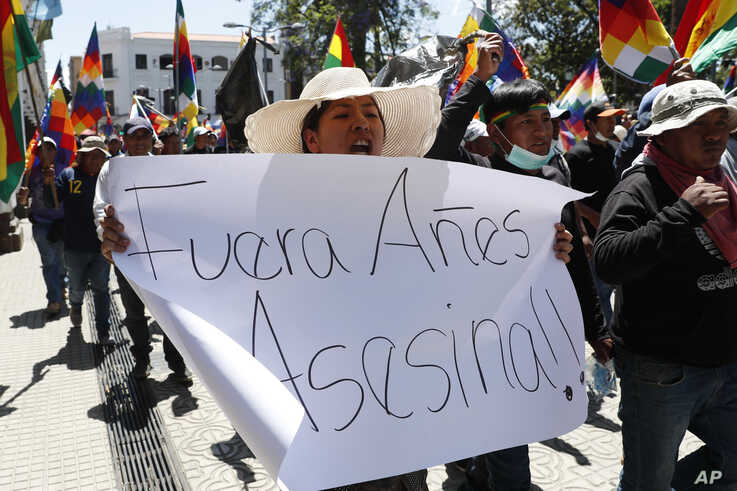 """A supporter of former President Evo Morales carries a sign reading in Spanish """"Out, Anez. Murderer"""" referring to interim president Jeanine Anez during a protest in Cochabamba, Bolivia, Nov. 18, 2019."""