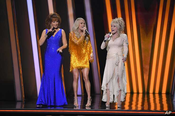 From left, Hosts Reba McEntire, Carrie Underwood and Dolly Parton appear at the 53rd annual CMA Awards at Bridgestone Arena, in Nashville, Tennesee, Nov. 13, 2019.