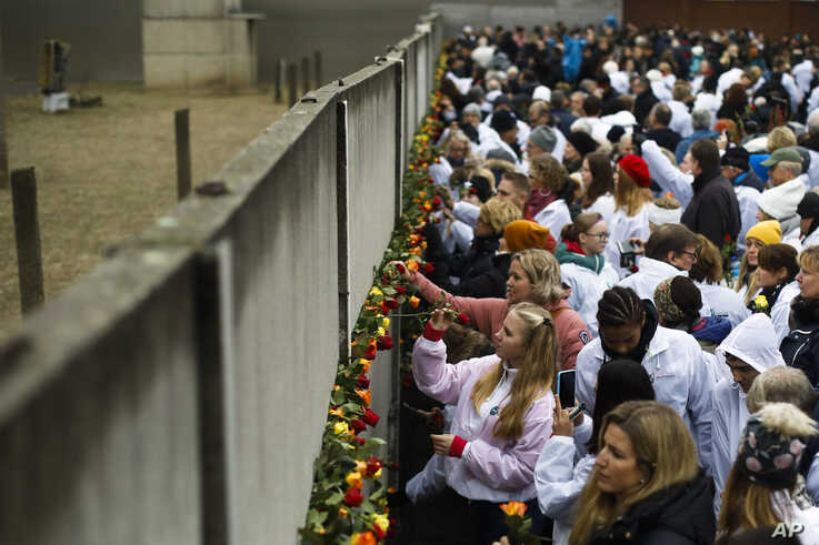 People stuck flowers in remains of the Berlin Wall during a commemoration ceremony to celebrate the 30th anniversary of the fall of the Berlin Wall at Bernauer Strasse in Berlin, Germany, Nov. 9, 2019.