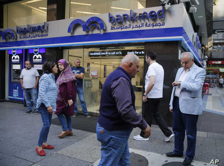 Clients wait outside a bank for its re-opening after a two-week closure, in Beirut, Lebanon, Nov. 1, 2019.