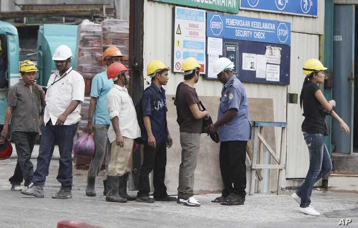 FILE - Workers are searched by security guards as they leave a construction site in a Kuala Lumpur suburb, Malaysia, March 23, 2010.