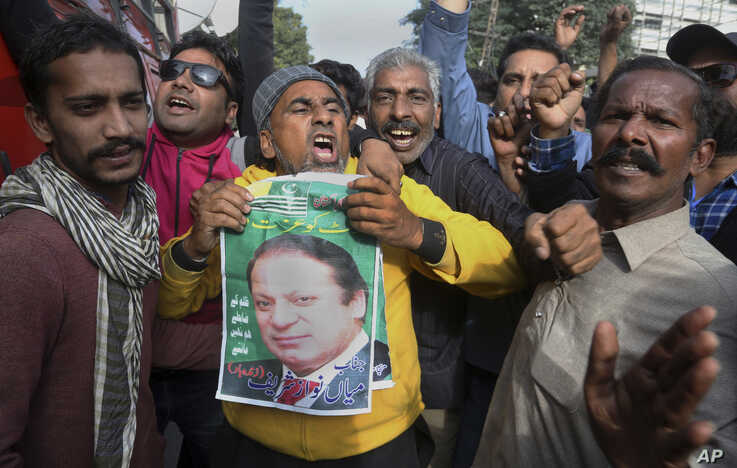 FILE - Supporters of former Pakistani Prime Minister Nawaz Sharif chant slogans outside the Lahore High court, in Lahore, Pakistan, Nov. 16, 2019.