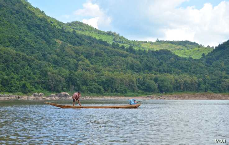A man fishes in the Mekong River near Houaygno village in northern Laos, where the government plans to build the Luang Prabang hydropower dam. (Zsombor Peter/VOA)