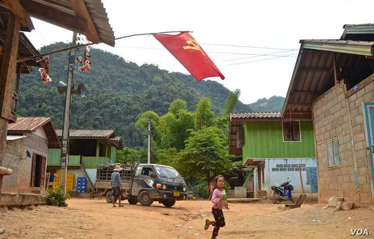 A girl runs across the street in Khokkham, one of six villages in northern Laos to be entirely flooded by the construction of the Luang Prabang dam. (Zsombor Peter/VOA)
