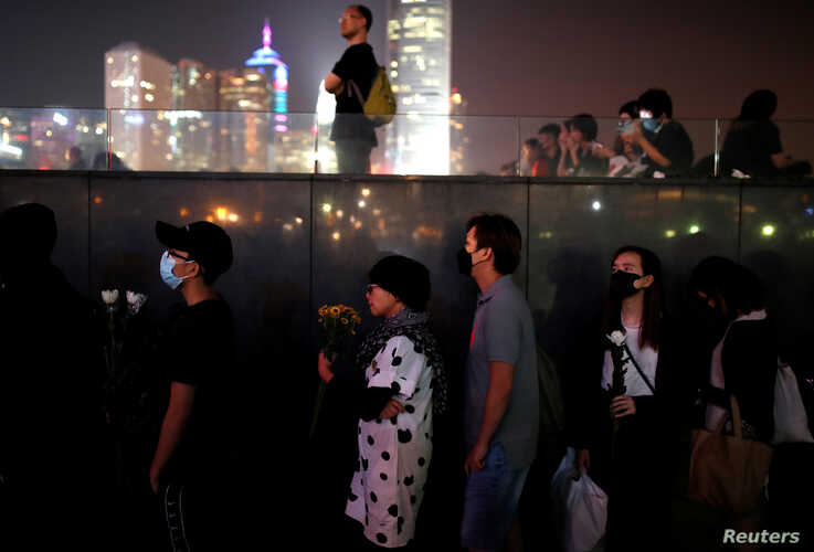 People line up to pay tribute at Tamar Park, outside the Legislative Council (Legco) building, during a prayer and remembrance ceremony in Hong Kong, China, Nov. 9, 2019.