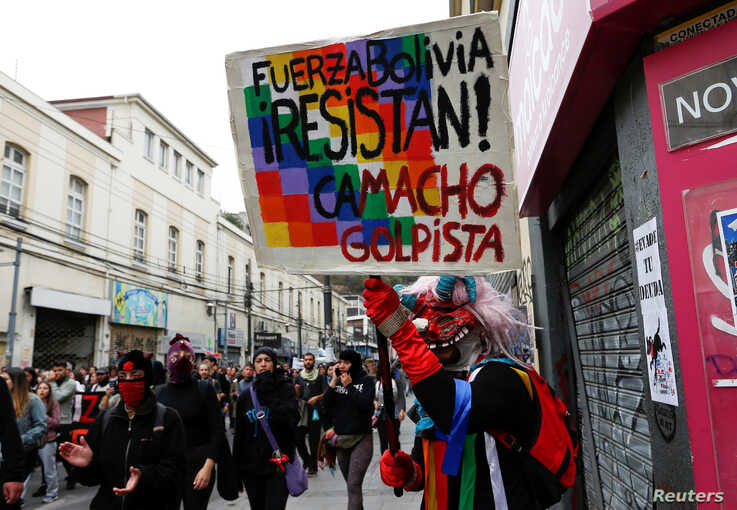 A demonstrator holds a placard that reads
