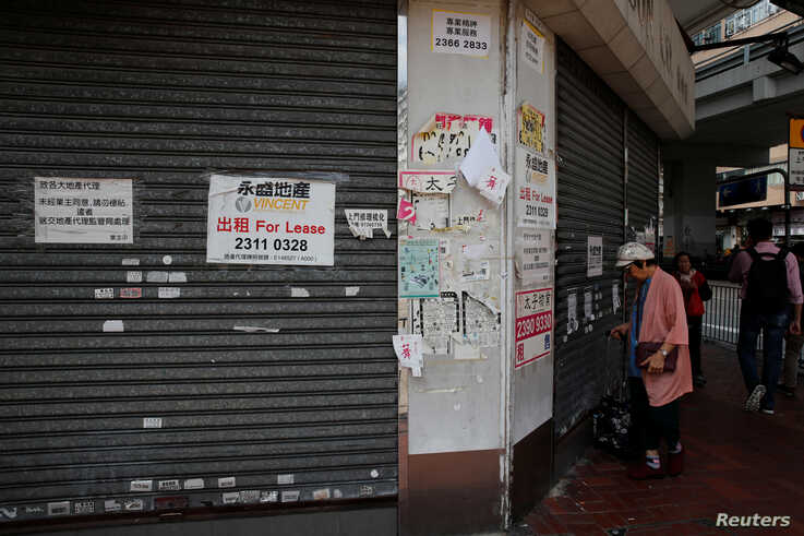 AA woman stands in front of a closed shop available for lease in Hong Kong, China, Oct. 29, 2019.