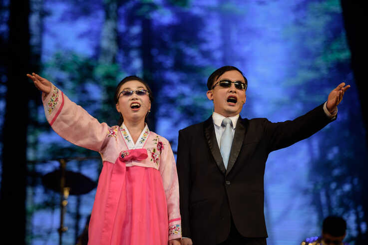 In a photo taken on December 3, 2019 visually-impaired singers Pae Ok Rim (L), 25, and Ri Kang Ryong 33, perform during an…