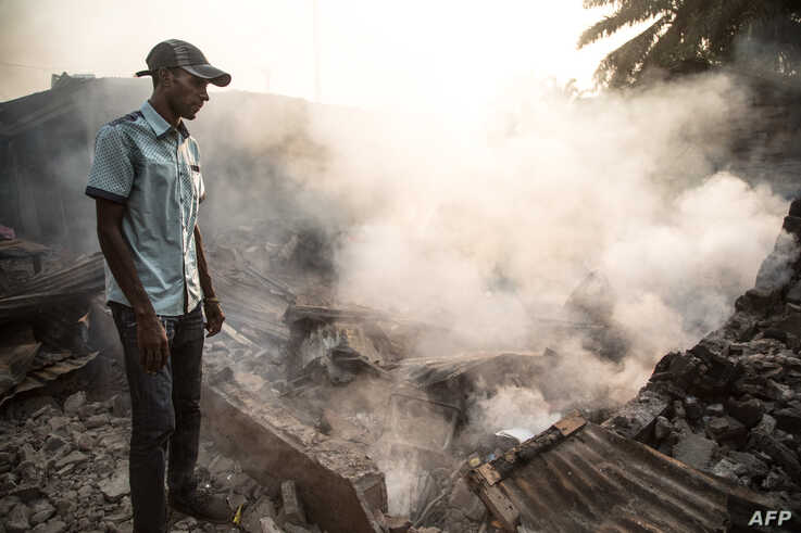 A man stand in front of a burnt down house in the PK5 district in Bangui on December 26, 2019, after clashes erupted when…