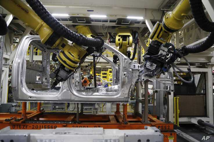 In this Sept. 27, 2018, file photo, robots weld the cab of a 2018 Ford truck on the assembly line at the Ford Rouge assembly plant in Dearborn, Michigan.