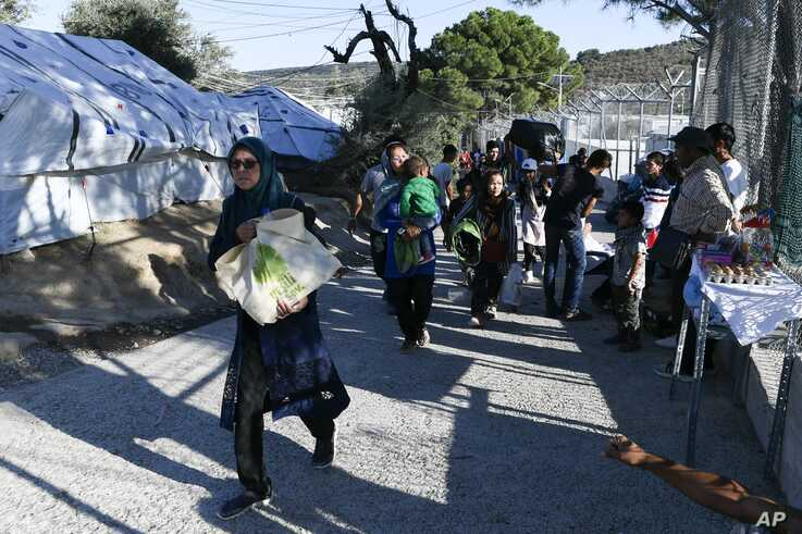 Migrants and refugees arrive at the Moria refugee camp, on the northeastern Aegean island of Lesbos, Greece, Monday, Sept. 23,…