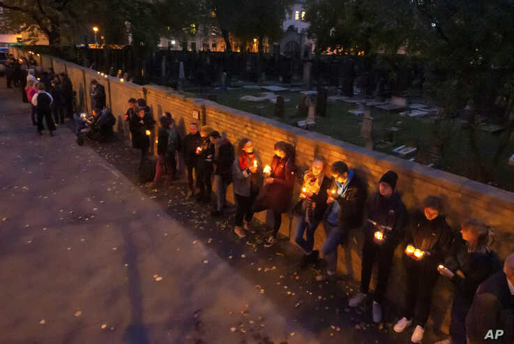 People line up for a human chain around the Jewish synagogue and the cemetery during the Sabbath celebrations in Halle, Germany, Oct. 11, 2019.