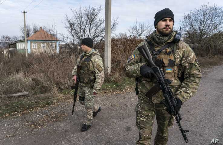 Ukrainian policemen patrol a street near the new line of contact in Katerynivka, Luhansk region, eastern Ukraine