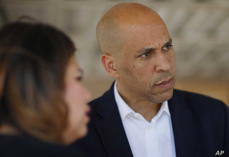 FILE - In this April 20, 2019 file photo Democratic presidential candidate Sen. Cory Booker, right, speaks with Astrid Silva,…