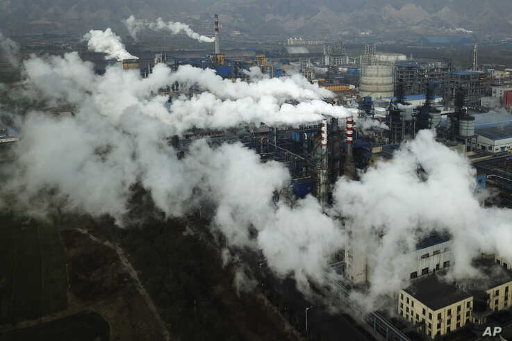 In this Nov. 28, 2019, photo, smoke and steam rise from a coal processing plant that produces carbon black, an ingredient in…