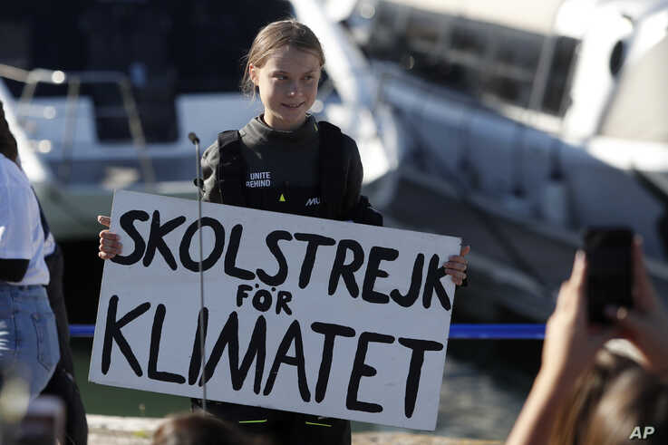 Climate activist Greta Thunberg holds a sign reading 'School strike for the climate' after arriving in Lisbon.