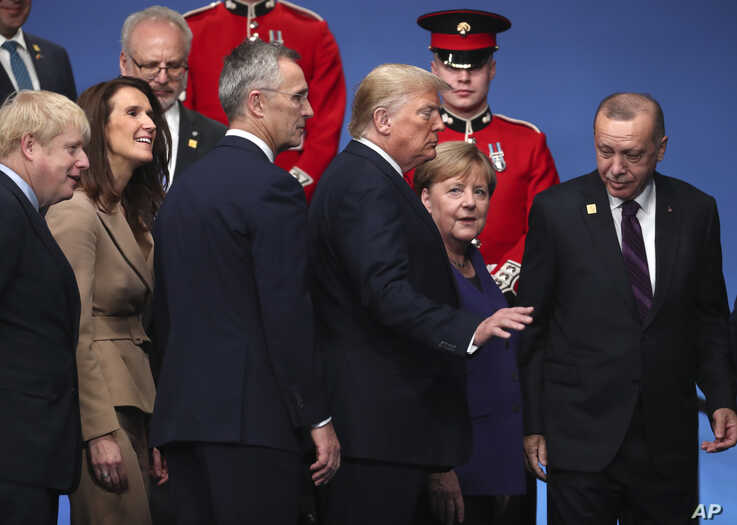 U.S. President Donald Trump, center left, speaks with German Chancellor Angela Merkel, center right, during a ceremony event.
