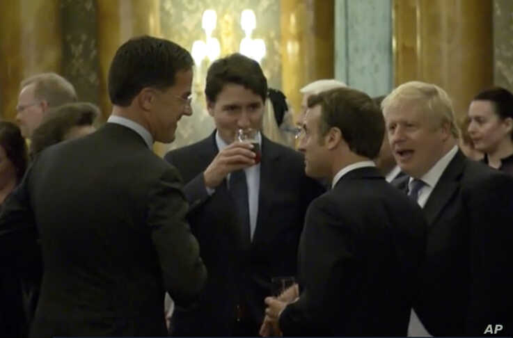 In this grab taken from video on Dec. 3, 2019, Britain's Prime Minister Boris Johnson, right, speaks during a party.