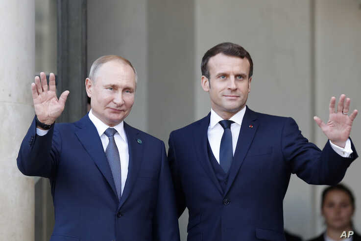 French President Emmanuel Macron, right, and Russian President Vladimir Putin wave at the Elysee Palace Monday, Dec. 9, 2019 in…