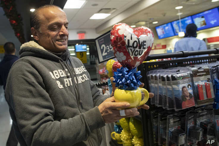 In this Tuesday, Dec. 3, 2019, photo, Mohammed Hafar buys a gift for his daughter Jana Hafar while waiting for her flight at…