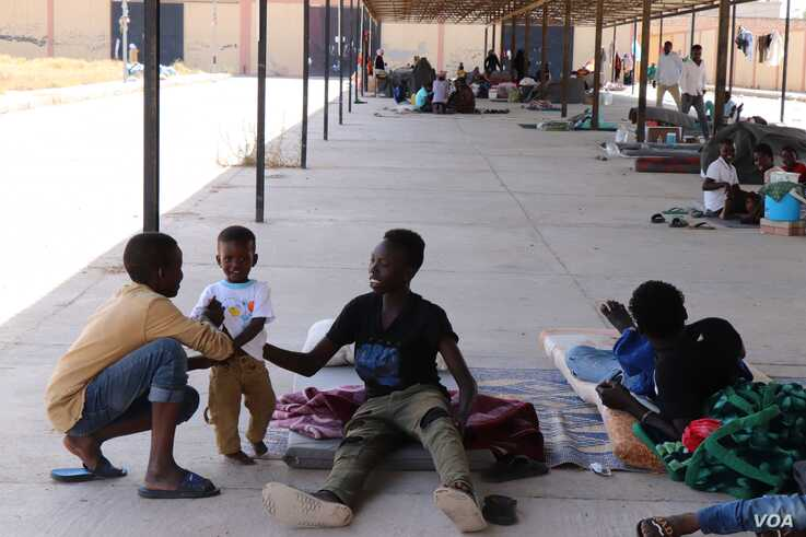 After fleeing the war in Libya, these families who also fled war, genocide and other violence in Sudan and Eritrea, sheltered under an awning in a parking lot, with no where else to go on July 5, 2019 in Tripoli, Libya. (H.Murdock/VOA)