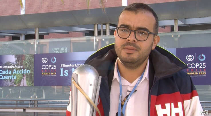 Moroccan activist Ayoub Makhloufi holding an eco-friendly torch, transported between each climate conference, like the Olympic one. Lisa Bryant. (L. Bryant/VOA)