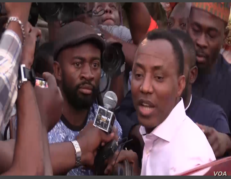 Journalists and supporters surround Omoyele Sowore just outside Department of State Security headquarters in Abuja, Nigeria, Dec. 24, 2019. (Timothy Obiezu/VOA)