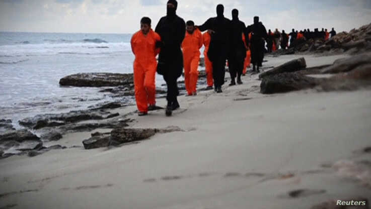 Men in orange jumpsuits purported to be Egyptian Christians held captive by the Islamic State (IS) are marched by armed men…