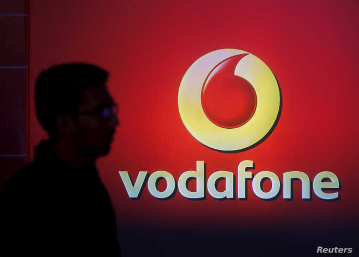 FILE PHOTO: A man casts silhouette onto an electronic screen displaying logo of Vodafone India after a news conference to…