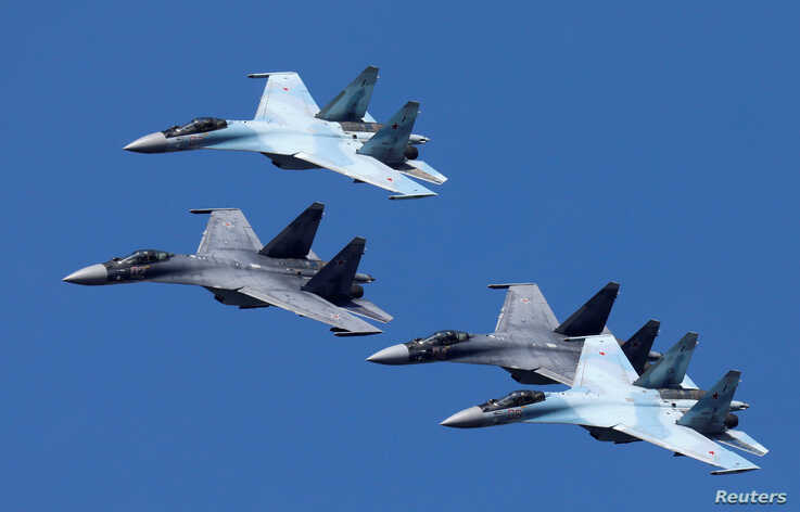 """Sukhoi Su-35 jet fighters of the """"Sokoly Rossii"""" (Falcons of Russia) aerobatic team fly in formation during a rehearsal for the…"""