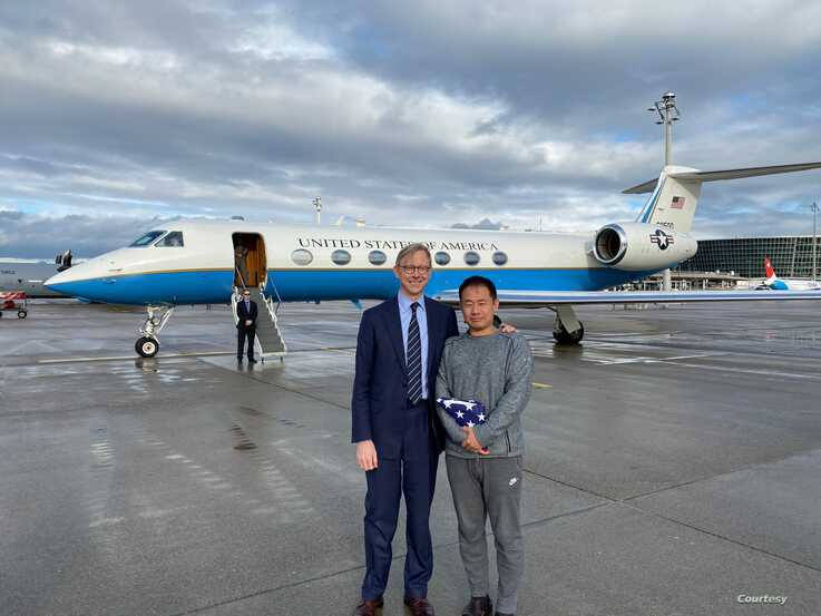 Chinese American academic Xiyue Wang, released by Iran after three years in jail as part of a prisoner swap with the U.S., stands with U.S. Special Representative for Iran Brian Hook at Zurich airport on December 7, 2019.