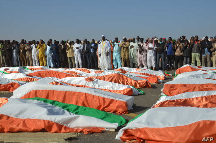 The Imam of the Great Mosque of Niamey, Cheikh Djabir Ismaël (C), stands in front of the bodies of military personnel during a funeral prayer at the Niamey Airforce Base in Niamey, Niger, Dec 13, 2019.