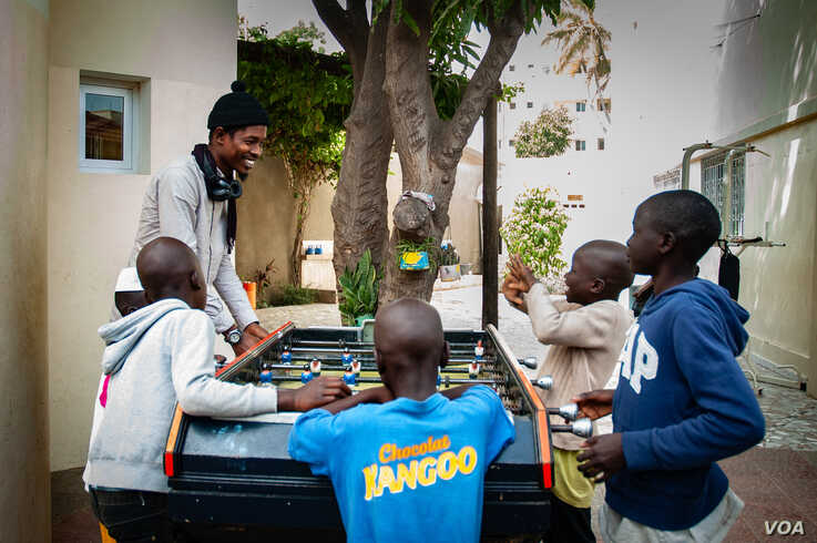 Talibés who were abused by their teachers play with Alassane Diagne, a coordinator at their shelter, Dec. 12, 2019, in Dakar, Senegal. (Annika Hammerschlag/VOA)