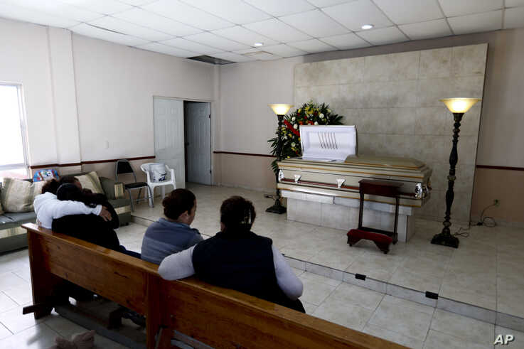 Family and friends attend the wake of a person who died during a gunbattle in Villa Union, Mexico, Dec. 2, 2019.