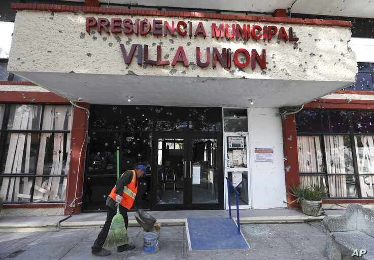 A worker cleans up outside City Hall, riddled with bullet holes, in Villa Union, Mexico, Dec. 2, 2019.