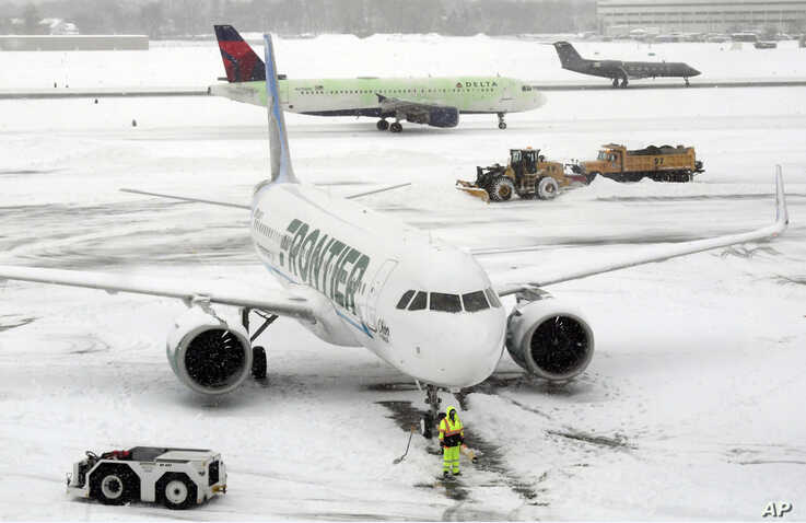 Ground crews remove snow from the airport tarmac as flights resume after an overnight snowfall, at the Albany International Airport in Colonie, N.Y., Dec. 2, 2019.